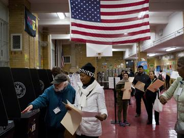 Poll worker Arlen Baden, left, assists a voter, Tuesday, Nov. 6, 2018, in the Brooklyn borough of New York.