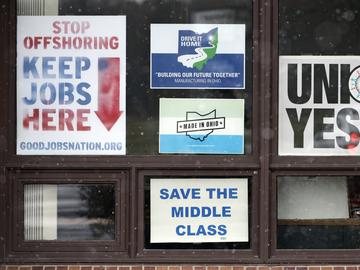 In this Nov. 27, 2018 photo, signs hang from windows at the UAW Local 1112 union hall, in Lordstown, Ohio.