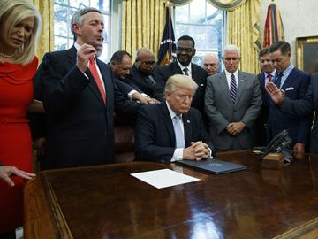 In this Sept. 1, 2017 file photo, religious leaders pray with President Donald Trump after he signed a proclamation for a national day of prayer to occur.