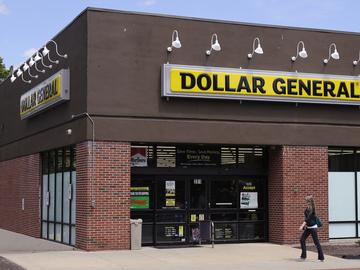 In this Wednesday, May 18, 2016, file photo, a woman walks past a Dollar General store in Methuen, Mass.