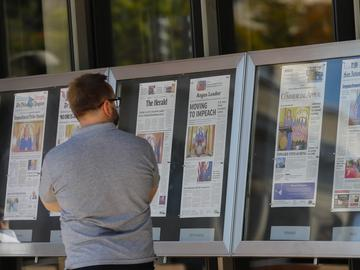 A man stops to look at newspaper front pages, from around the US, on display at the Newseum in Washington, Wednesday, Sept. 25, 2019.