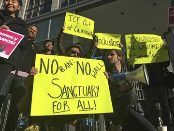 In this April 14, 2017, file photo, protesters hold up signs outside a courthouse in San Francisco.