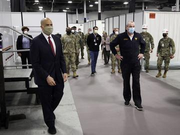 Sen. Cory Booker, D-N.J., left, and New Jersey Gov. Phil Murphy, right, tour the Edison Field Medical Station at the site of the N.J. Convention & Exposition Center in Edison, N.J.