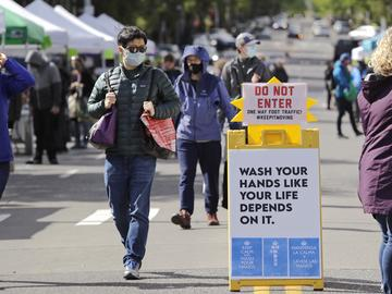 Masked customers walk through the West Seattle Farmers Market during its first opening in nearly two months because of the coronavirus outbreak Sunday, May 3, 2020, in Seattle.