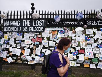 A woman passes a fence outside Brooklyn's Green-Wood Cemetery adorned with tributes to victims of COVID-19, Thursday, May 28, 2020, in New York.