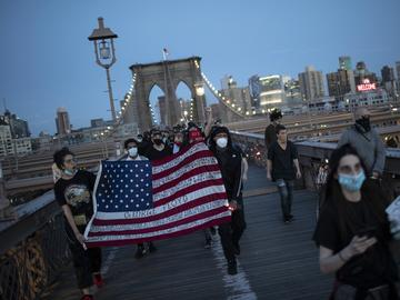 Protesters march across the Brooklyn Bridge as part of a solidarity rally calling for justice over the death of George Floyd Monday, June 1, 2020, in the Brooklyn borough of New York.