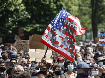 A protester waves an American flag with a message that reads 'CAN'T BREATHE' during a memorial for George Floyd at Cadman Plaza Park in the Brooklyn borough of New York, on Thursday, June 4, 2020.