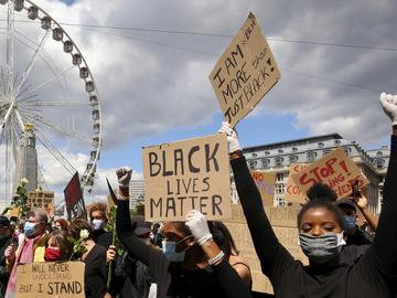 Protesters hold placards during the Black Lives Matter protest rally in Brussels, Sunday, June 7, 2020. The demonstration was held in response to the recent killing of George Floyd by police officers