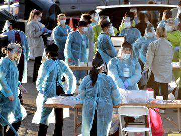In this June 27, 2020, file photo, medical personnel prepare to test hundreds of people lined up in vehicles in Phoenix's western neighborhood of Maryvale for free COVID-19 tests.