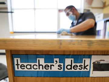 Des Moines Public Schools custodian Joel Cruz cleans a teacher's desk in a classroom at Brubaker Elementary School, Wednesday, July 8, 2020, in Des Moines, Iowa.