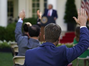 Reporters raise their hands to ask questions as President Donald Trump speaks during a news conference in the Rose Garden of the White House, Tuesday, July 14, 2020, in Washington.