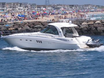 In this June 28, 2020, a yacht cruises through the Manasquan Inlet as a large crowd fills the beach in Manasquan, N.J.