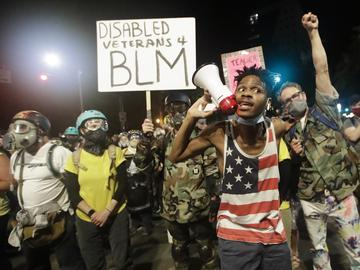 A demonstrator shouts slogans using a bullhorn next to a group of military veterans during a Black Lives Matter protest at the Mark O. Hatfield United States Courthouse July 26, 2020, in Portland, OR.
