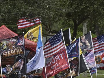 Flags and banners line the street outside of the campaign rally where President Donald Trump will speak at a rally, Thursday, Sept. 24, 2020, in Jacksonville, Fla.