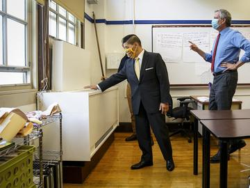 School Chancellor Richard Carranza, left, feels for airflow from a ventilation unit inside a classroom at Bronx Collaborative High School, during a visit with Mayor Bill de Blasio, right, to review he