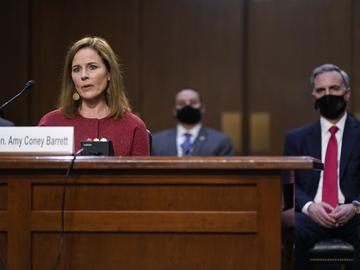 Supreme Court nominee Amy Coney Barrett speaks during a confirmation hearing before the Senate Judiciary Committee, Tuesday, Oct. 13, 2020, on Capitol Hill in Washington. Her family looks on at left.
