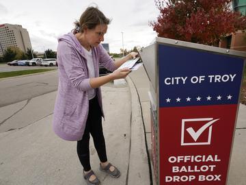 Nikki Schueller inserts her absentee voter ballot into a drop box in Troy, Mich., Thursday, Oct. 15, 2020.