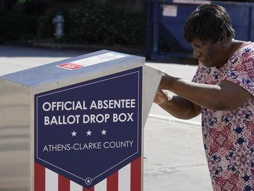 A voter drops their ballot off during early voting, Monday, Oct. 19, 2020, in Athens, Ga. With record turnout expected for this year's presidential election and fears about exposure to the coronavirus