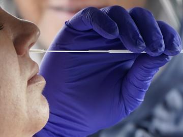Salt Lake County Health Department public health nurse Lee Cherie Booth performs a coronavirus test outside the Salt Lake County Health Department on Friday, Oct. 23, 2020, in Salt Lake City.