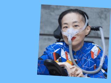 Alice Wong in a power chair. She wears a blue shirt with a pattern of orange, black, white, and yellow lines and cubes. She's masked, but smiling with red lips. The mask is attached to a gray tube.