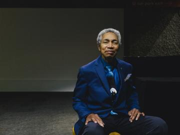 Musician Beverly Glenn-Copeland sits in a chair facing the camera. He's an older Black man with a short gray Afro, and wears a blue suit, dress shirt, and tie.