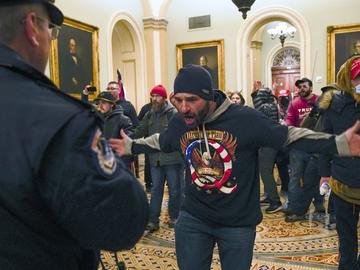 Trump supporters gesture to U.S. Capitol Police in the hallway outside of the Senate chamber at the Capitol in Washington, Wednesday, Jan. 6, 2021.