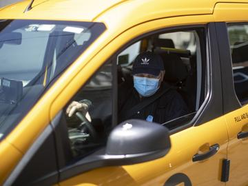 Taxi driver Nicolae Hent, wearing a protective mask, drives his taxi in New York, Monday, April 6, 2020.