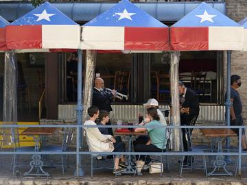 Mariachi perform for diners at a restaurant on the River Walk, Wednesday, March 3, 2021, in San Antonio. Gov. Greg Abbott says Texas is lifting a mask mandate and lifting business capacity limits next