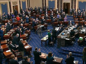 In this image from video, senators stand and applaud support staff, before the final vote on the Senate version of the COVID-19 relief bill in the Senate at the U.S. Capitol in Washington, Saturday.