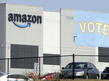 In this March 30, 2021 file photo, a banner encouraging workers to vote in labor balloting is shown at an Amazon warehouse in Bessemer, Ala.