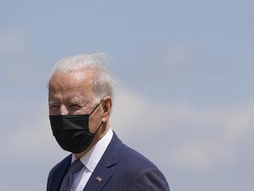 Joe Biden wears a black face mask and a navy suit. He looks into the distance, with blue sky in the background.
