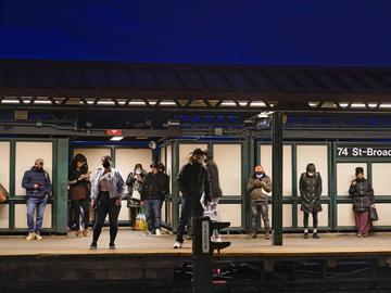 In this April 22, 2021 file photo, patrons wait for the #7 train at the 74th street subway station in the Queens borough of New York.