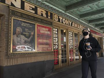 A woman walks past the Walter Kerr Theatre, Thursday, May 6, 2021, in New York where Hadestown was showing before the coronavirus pandemic forced its closing a year ago.