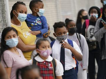 In this Sept. 9, 2020, file photo, students wear protective masks as they arrive for classes at the Immaculate Conception School while observing COVID-19 prevention protocols in The Bronx.