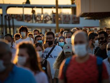 a crowd of people at sunset mostly wearing masks