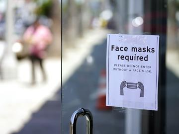 A sign advises shoppers to wear masks outside of a store Monday, July 19, 2021, in the Fairfax district of Los Angeles.