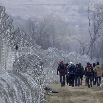Refugees and migrants, including Syrians, walk between the two lines of the protective fence along the border line in Macedonia in 2016.