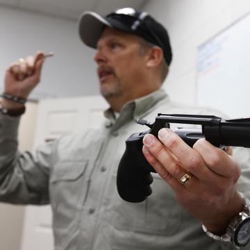 Gun instructor Mike Stilwell demonstrates a revolver as he teaches a packed class to obtain the Utah concealed gun carry permit, at Range Master of Utah, on January 9, 2016 in Springville, Utah.