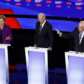 Sen. Elizabeth Warren, D-Mass., left, and Sen. Bernie Sanders, I-Vt., right speak as former Vice President Joe Biden listens Tuesday, Jan. 14, 2020.