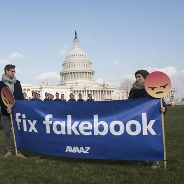 Men with sign saying 'Fix fakebook' stand next to  of 100 cardboard Mark Zuckerbergs in front of the U.S. Capitol