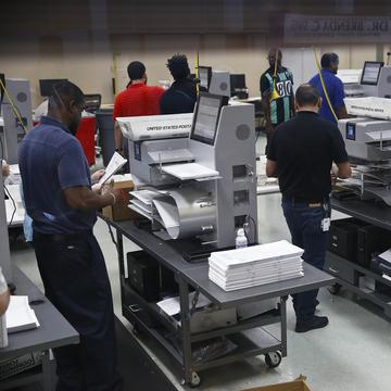 Workers load ballots into machines at the Broward County Supervisor of Elections office during a recount on Sunday, Nov. 11, 2018, in Lauderhill, Fla.