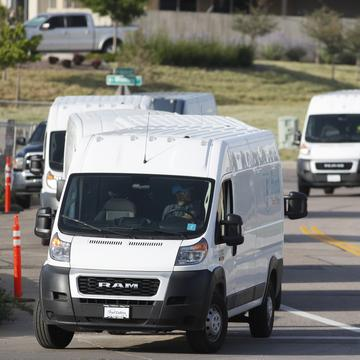 In this Tuesday, July 30, 2019, file photograph, vans queue up to leave an Amazon delivery center in suburban Englewood, Colo.