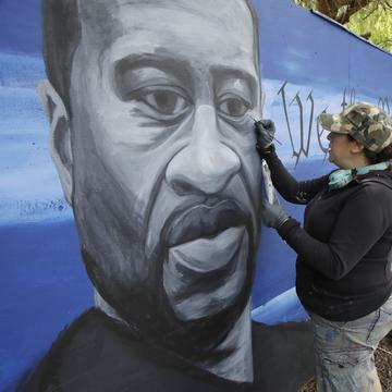 Artist Melissa Penny paints a mural depicting George Floyd as her daughter Anabelle Penny watches on Wednesday, June 10, 2020, in Vallejo, Calif.