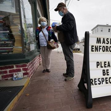 Shoppers comply with the mask regulations to help prevent the spread of the coronavirus at Bridgton Books, Friday, Nov. 13, 2020, in Bridgton, Maine.