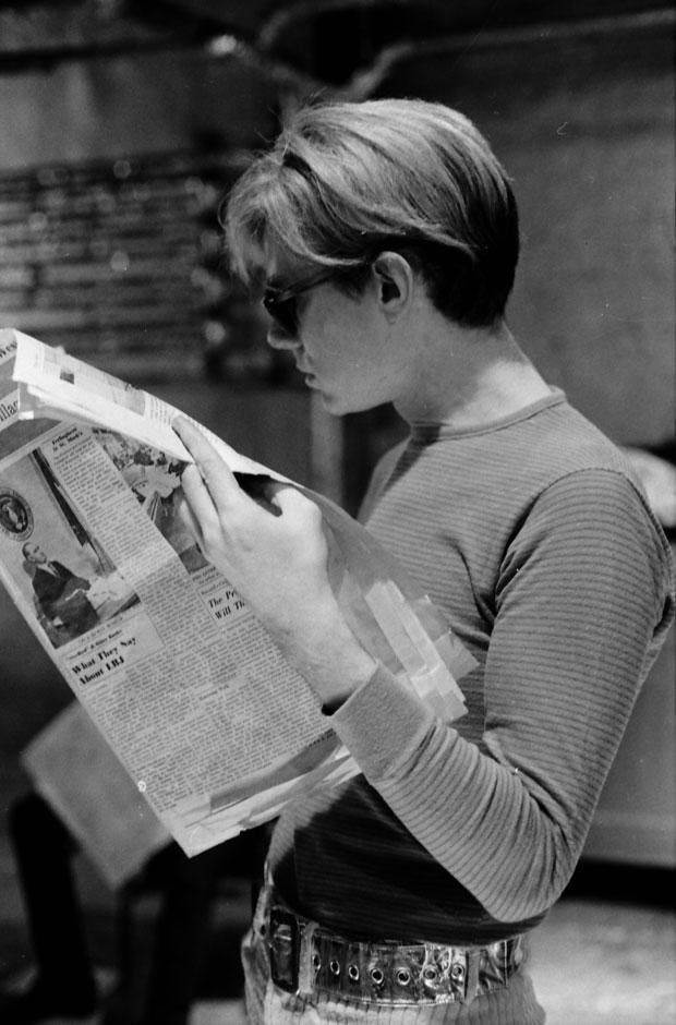 Andy Warhol reading the Village Voice in the Silver Factory, 1966.