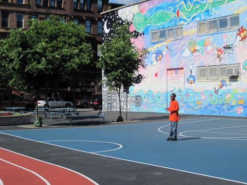 Kyle Broomes shows off the renovated playground, shared by FLI charter and PS 242