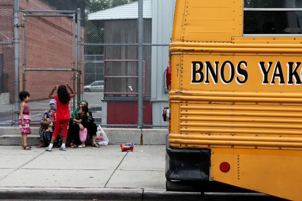 A school bus and children playing across the street from Levi Aron's home.