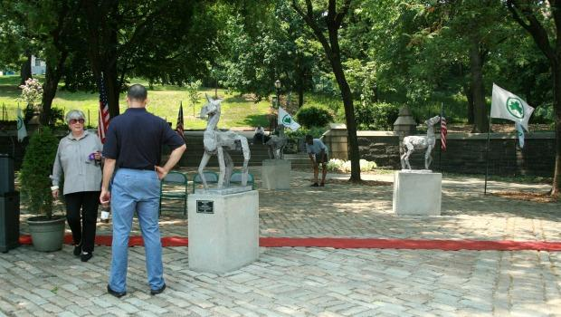 Passers-by examine the sculptures at the entrance to the park.