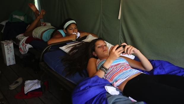 Female campers uses iPhone at summer camp