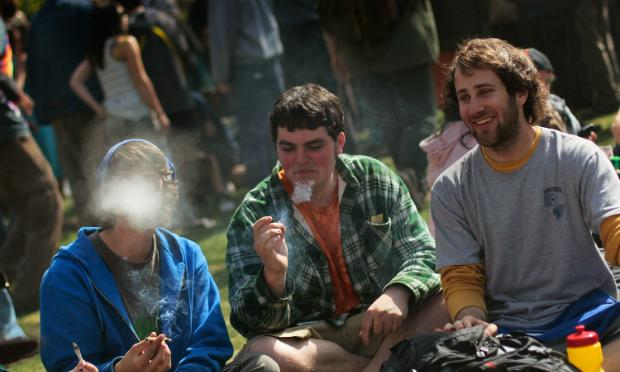 Young men smoke a marijuana cigarette during a 'smoke out' with thousands of others April 20, 2010 at the University of Colorado in Boulder, Colorado